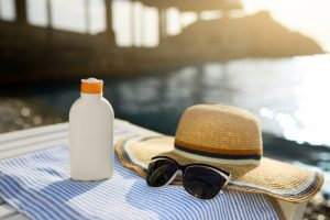 suntan cream bottle and sunglasses on beach towel with sea shore on background-img-blog