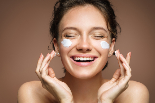 laughing girl applying moisturizing cream on her face-img-blog