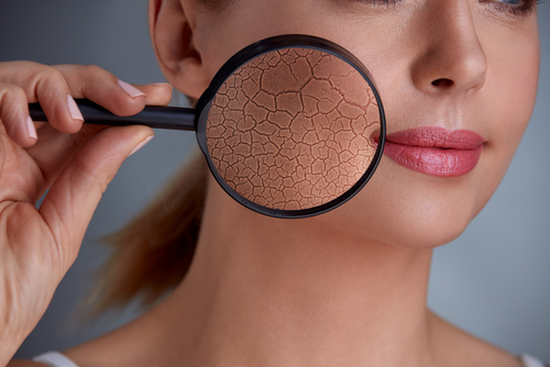 woman holding magnifier and zoom damage on skin-img-blog