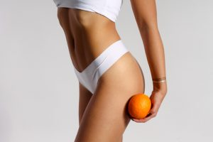 Mid section of woman with sport body holding orange near her leg