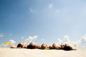 five teens lying on the sand and sunbathing