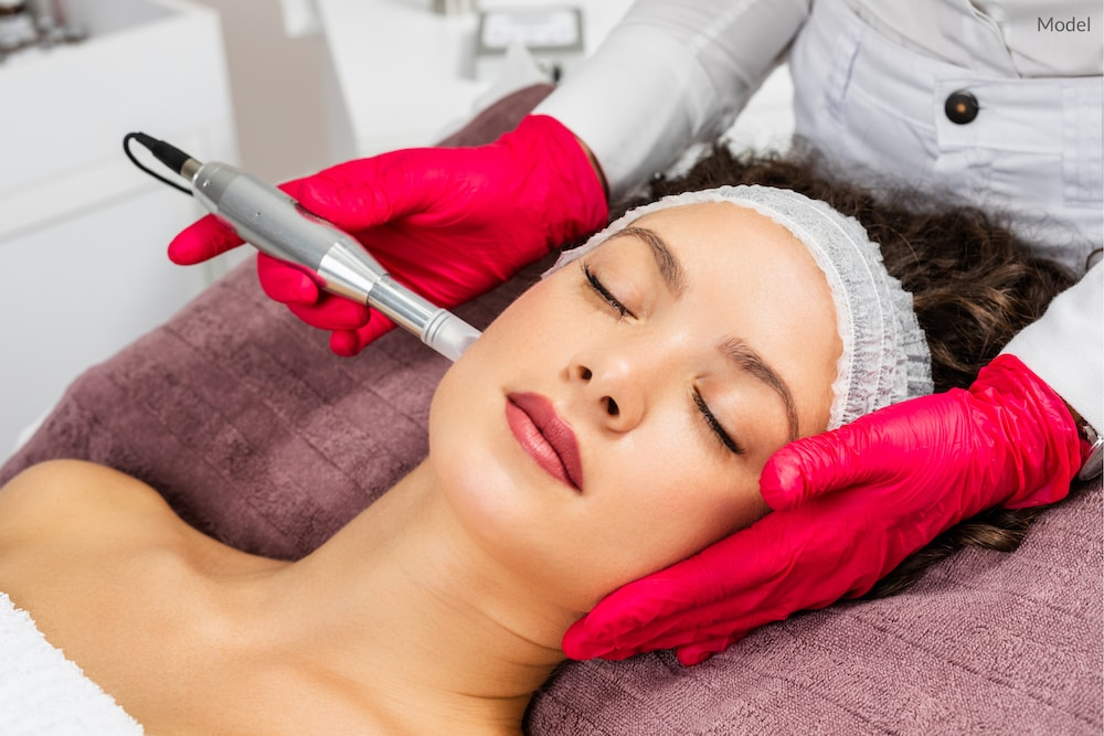 Woman undergoing microneedling treatment at a medical spa.
